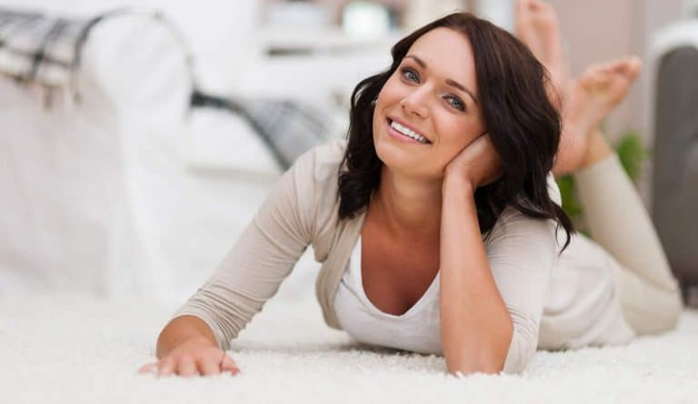 Smiling woman lying on carpet